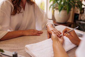 Nail technician giving customer