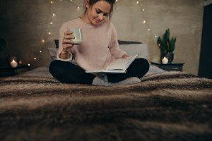 Relaxed woman on bed reading