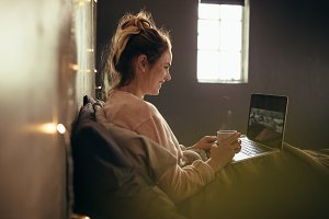 Woman on bed using laptop