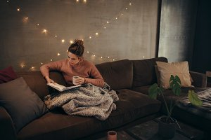 Woman reading book in cozy