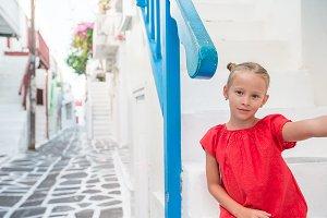 Adorable girl taking selfie photo outdoors in greek village on narrow street
