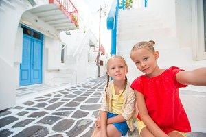 Two little girls taking selfie photo outdoors in greek village on narrow street in Mykonos