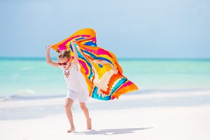 Adorable little girl having fun running with pareo on tropical white beach