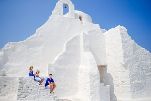 Happy family near Paraportiani church on Mykonos Island, in Greece