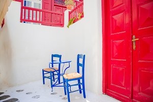 Outdoor cafe with blue chairs on street of typical greek traditional village on Mykonos Island, Europe