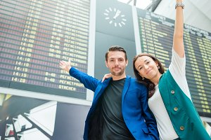 Family of two in international airport background the flight information board