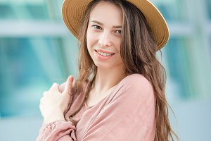 Young woman in international airport. Portrait of beautiful tourist girl in hat ready to fly