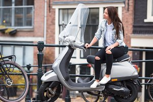 Young woman on a moped on the bridge over the canal in Amsterdam