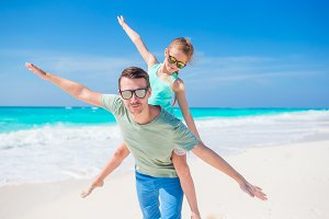 Little girl and happy father having fun during beach vacation