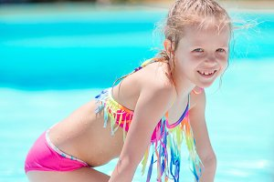 Little active adorable girl in outdoor swimming pool ready to swim