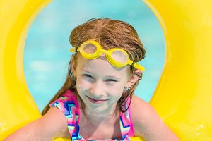 Little girl with inflatable rubber circle having fun in outdoor swimming pool