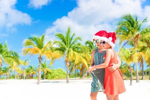 Adorable little kids have fun in Santa hat celebrating Christmas on the beach