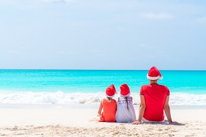 Happy beautiful family of father and kids in red Santa hats on a tropical beach celebrating Christmas holiday