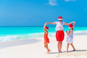 Happy beautiful family of mother and kids in red Santa hats on a tropical beach celebrating Christmas holiday