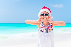 Happy little girl in Santa hat during Christmas beach vacation have a lot of fun