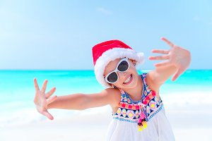 Happy little girl in Santa hat on Christmas beach vacation