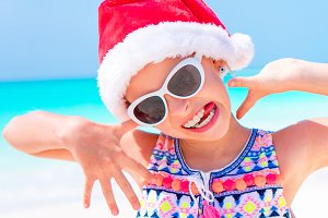 Happy funny little girl in Santa hat during Christmas beach vacation have a lot of fun