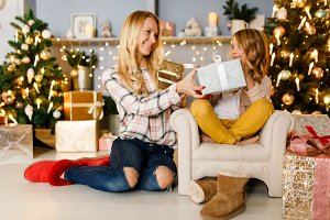 New Year's picture of happy mother giving gift to daughter sitting on armchair