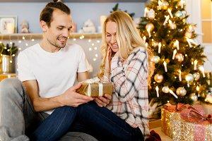 Sweet couple opening Christmas gifts