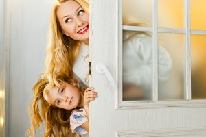 Picture of couple with daughter peeking out from behind door with Christmas wreath