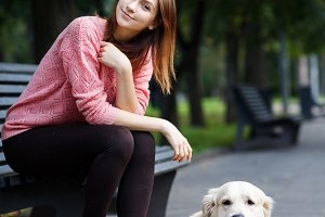 Photo of woman sitting on bench on walk with dog