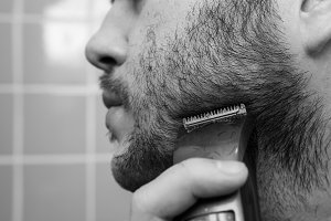 Portrait of young man shaving with trimmer