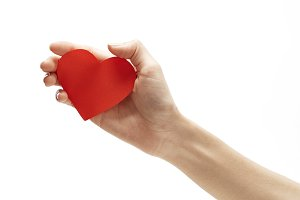 red paper heart in hand isolated on