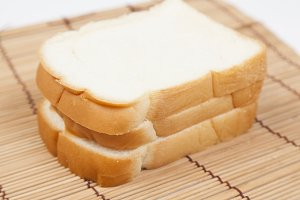 Sliced ​​bread on the wooden plate.
