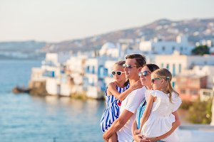 Family vacation. Parents and kids on Little Venice background on Mykonos Island, in Greece, Europe