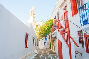 The narrow streets of the island with blue balconies, stairs and flowers in Greece. Beautiful architecture building exterior with cycladic style.