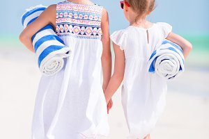 Adorable little girls with beach towels on white tropical beach