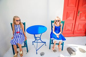 Two girls in blue dresses sitting in outdoor cafe on street of typical greek village on Mykonos Island, Greece