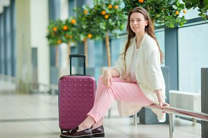 Young woman in international airport with her luggage and coffee to go waiting for her flight