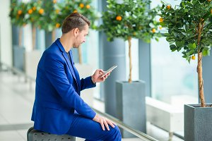 Young man with cellphone at the airport while waiting for boarding. Casual young boy wearing suit jacket.