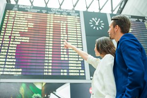 Young couple in international airport looking at the flight information board