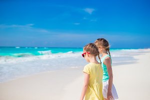 Little girls having fun at tropical beach playing together on the seashore
