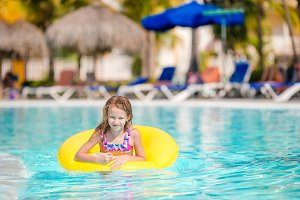 Little girl with inflatable rubber circle having fun in outdoor swimming pool in luxury hotel
