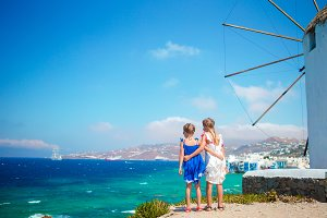 Adorable little girls with amazing view on Little Venice the most popular tourist area on Mykonos island