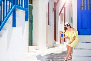 Young woman walking in narrow streets of old greek village in Greece