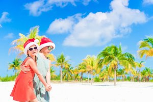 Happy kids have fun in Santa hat during Christmas beach vacation. New Year on the beach
