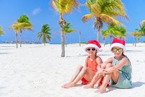 Adorable little kids in Santa hat during Christmas beach vacation. New Year on the beach