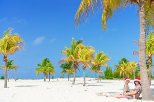 Young mom and little girl have fun at tropical beach in santa hat sitting near palm tree