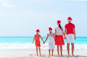Happy family in red Santa hats on a tropical beach celebrating Christmas vacation