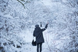 Girl walking in snow forest