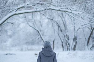 Girl walking in the snow forest