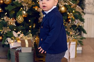 baby boy stands in a suit at Christmas at Christmas tree