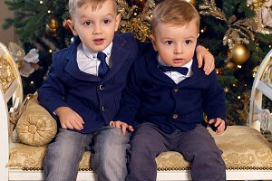 two brothers in suits sitting on the sofa