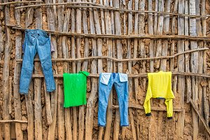 Clothes hanging on wall of a wooden hut in Africa