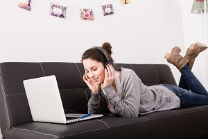 woman using laptop and listening mus