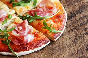 Pizza with smoked ham and rucola on wooden background